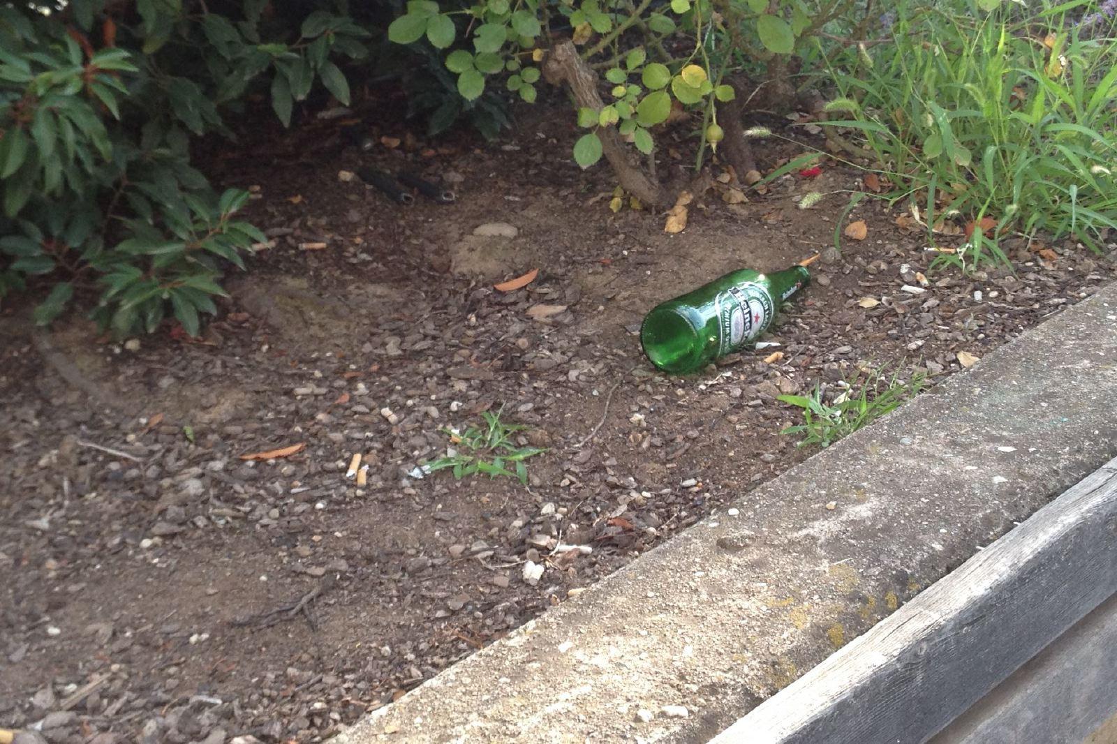Bottiglia vuota e cumuli di mozziconi