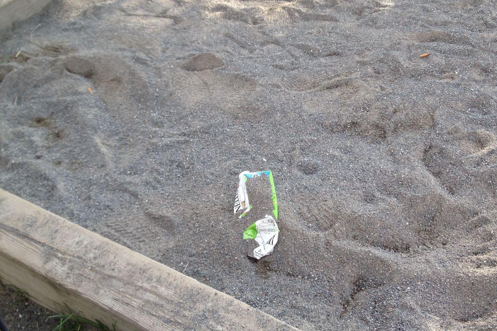 Cartone di vino e mozziconi della sabbia dei bambini